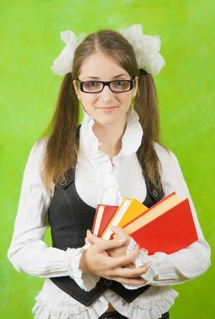teener: schoolgirl in glasses with books over green background Stock Photo