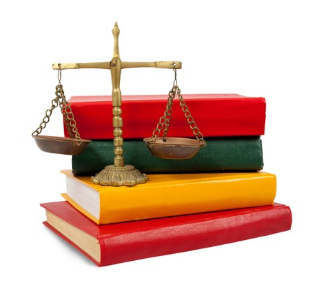 antique scales:  Scales of justice atop legal books over white
