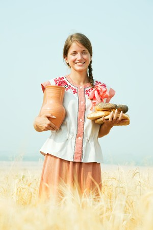 Girl with bread and jug of milk  at rye field photo