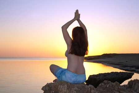 silhouette of girl doing yoga against sunset of a sun photo