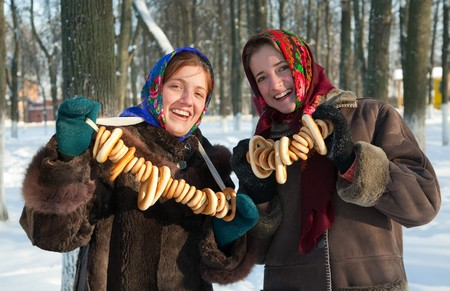 pancake week: Smiling girls with round cracknel during Pancake Week at Russia