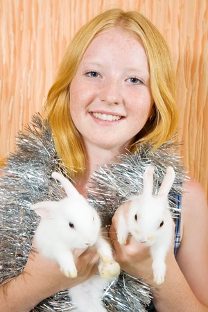 tawdry: Teen  girl with two pet rabbits sitting in home  Stock Photo