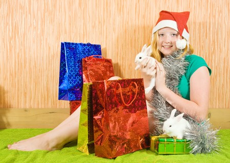 tawdry: teenager girl  with Christmas gifts and two pet rabbits
