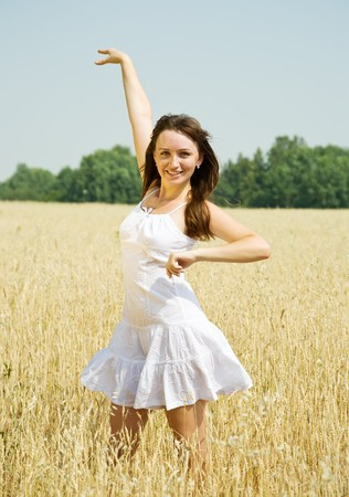 Standing girl  in white at cereals field in summer Stock Photo - 7529184