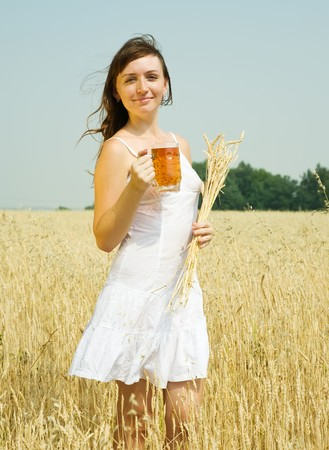 Girl  with beer at cereals field in summer photo