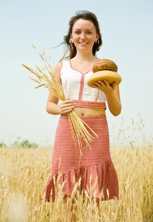 Girl in traditional clothes with bread  at wheat field photo