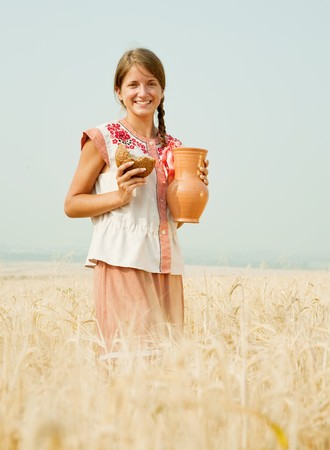 Girl in traditional clothes with bread and jug at rye field photo