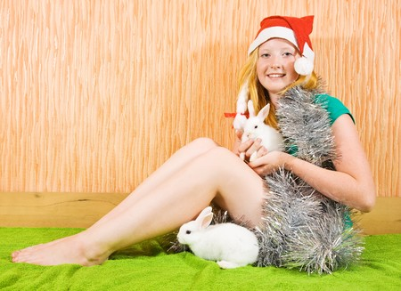 teenager girl in new year decoration with two pet rabbits Stock Photo - 7532188