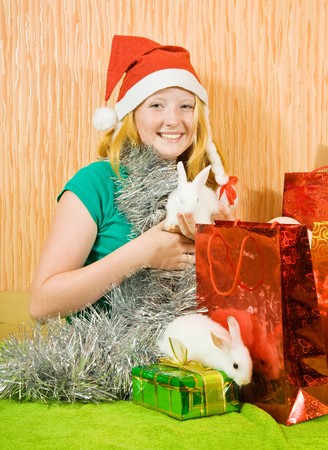 tawdry: teenager girl in new year decoration with two pet rabbits  Stock Photo