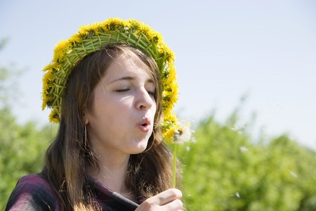 Young girl blowing seeds of a dandelion flower Stock Photo - 7557347