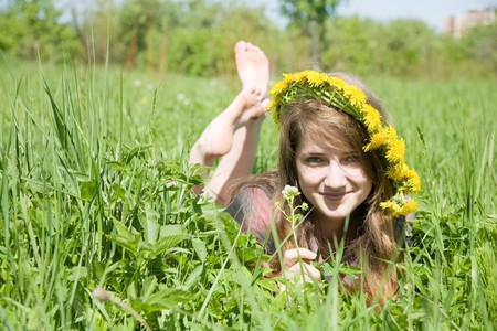 long-haired teen girl in a chaplet lying from meadow photo