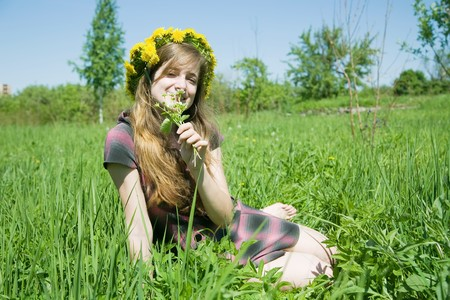 chaplet: long-haired teen girl  in a chaplet against a meadow Stock Photo