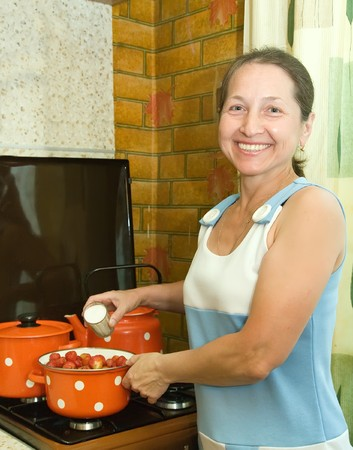 Woman preserving strawberry preserves  in the kitchen photo