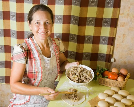 pasty: elderly woman cooking meat pasty at kitchen