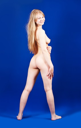 Standing long-haired blonde naked girl on blue background Stock Photo - 7582392