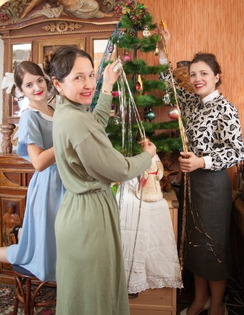 Teen girls with mother decorating Christmas tree at home photo