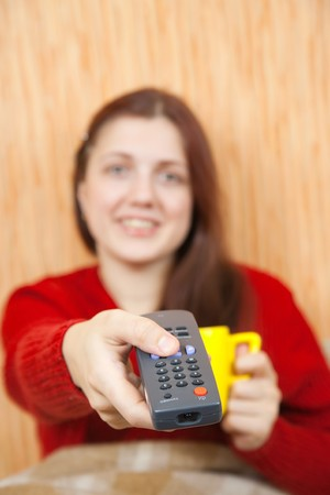 clicker: Young woman smiling with TV remote control . Focus on clicker