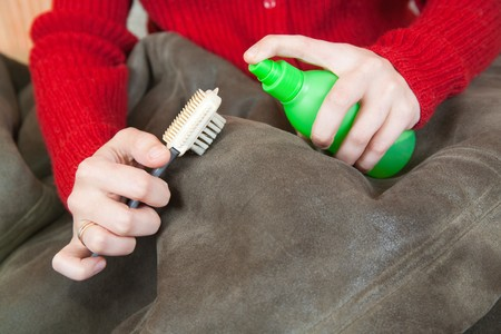 furskin: Closeup of Woman cleaning a sheepskin with whisk broom  Stock Photo