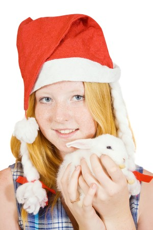 Teen girl  in santa hat with rabbit, isolated on white background photo