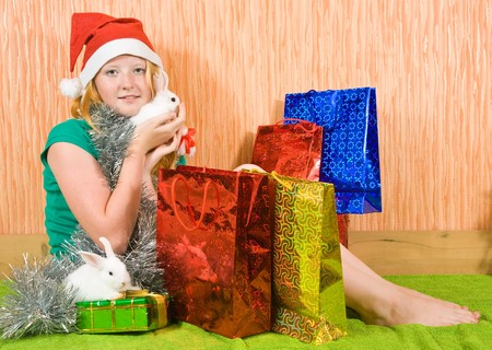 teenager girl   with Christmas gifts and two pet rabbits  photo