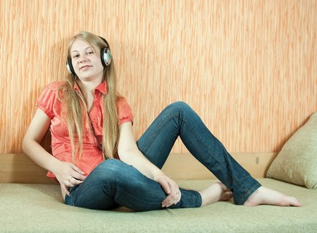 househould: Young beautiful happy girl listening music in headphones on  couch