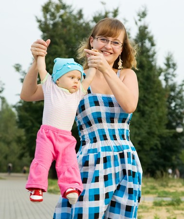 Happy mother playing with baby outdoor in summer Stock Photo - 7619328