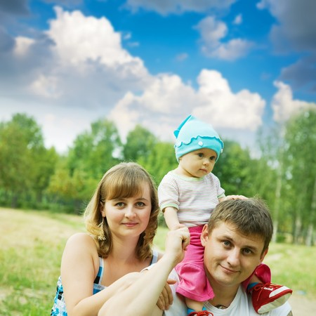 father and mother with baby at the park   photo