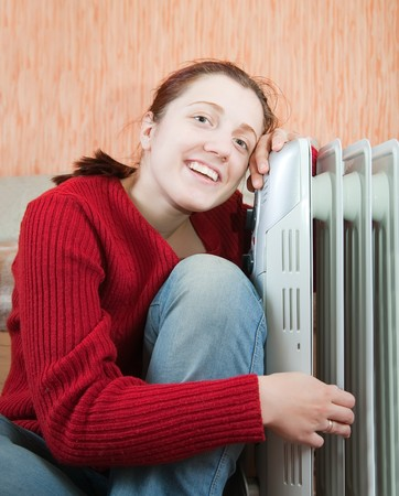 woolley: young smiling girl is sitting near oil heater