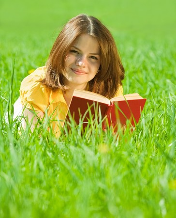 young  girl reading book in grass outdoors photo