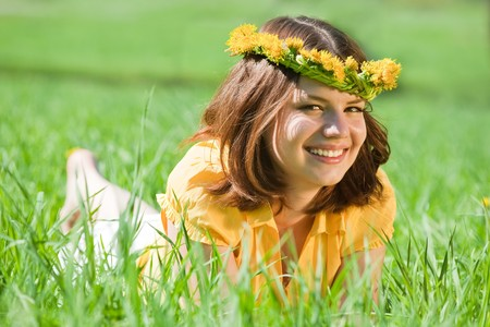 barefoot girl in dandelion  chaplet lying from meadow photo