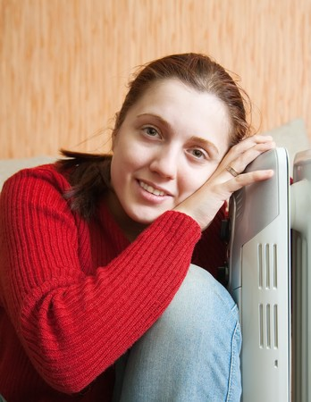 young smiling girl is sitting near oil heater
