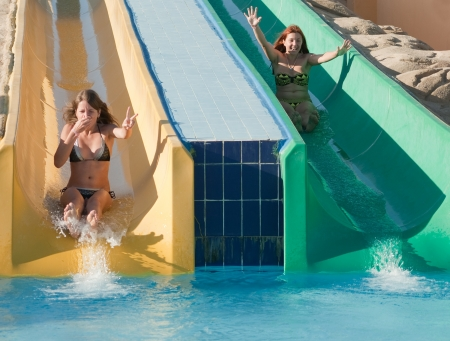 Young beautiful caucasian women in bikini on swimming pool water slide  photo