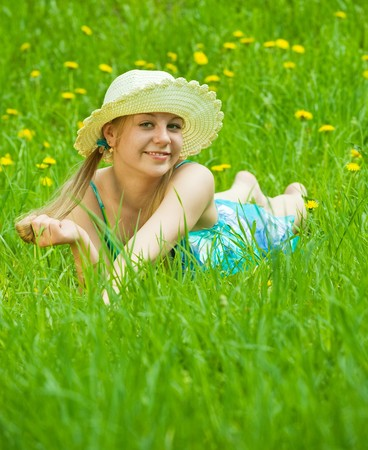 Pretty smiling  girl in hat relaxing in grass outdoor  photo