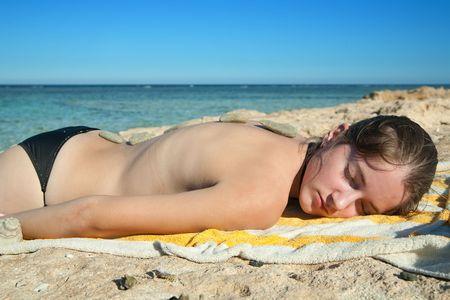 beauty girl enjoying a hot stone massage on the beach photo