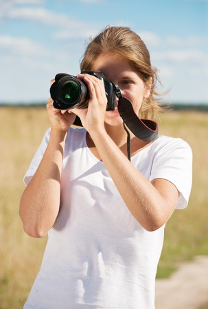 Young girl taking photo with camera against field photo