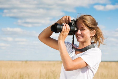若い女の子は青い空を背景写真を取る