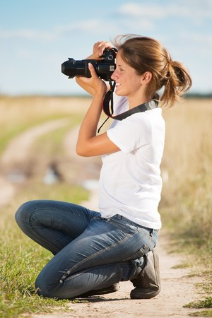 Young girl taking photo with camera against field Stock Photo