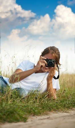 nature photography: Young girl taking photo with camera against blue sky Stock Photo