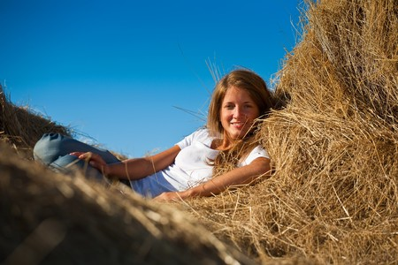 country girl on fresh hay at field photo