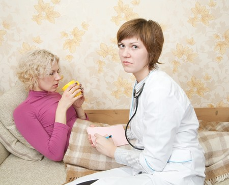 Female doctor loking to suffering girl on bed Stock Photo - 7661805