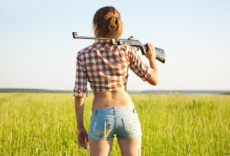 airsoft: young girl with air rifle against field