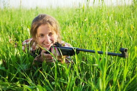 stunningly beautiful young woman   with air rifle in grass photo