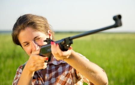 rifleman: chica con el objetivo de un rifle neum�tico contra el campo de verano  Foto de archivo