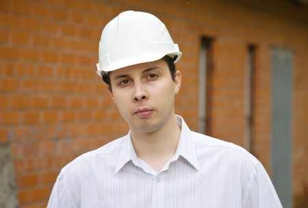 male construction worker in hard hat against  the brick wall photo