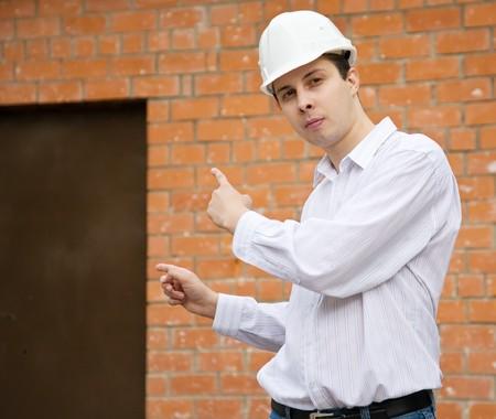 tasker: builder  in hard hat pointing to door in brick wall