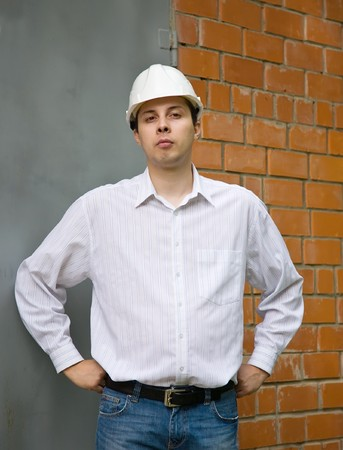 tasker: builder  in hard hat  gesticulating against  the brick wall Stock Photo