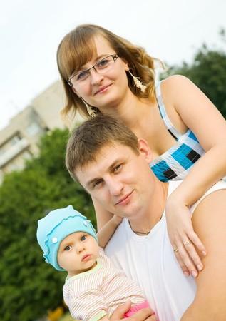 portrait of  happy family of three at city park photo