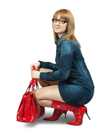 Girl in blue dress ang red high boots with purse.