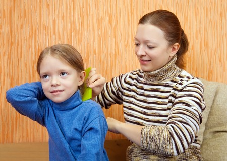 mother combs the hairs of daughter at home photo