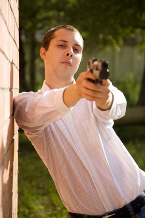 young man aiming a black gun  near  the brick wall Stock Photo - 7704705